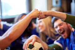 Soccer fans with ball celebrating victory at bar. People, soccer, leisure and sport concept - happy friends or football fans with ball celebrating victory at bar Royalty Free Stock Photos
