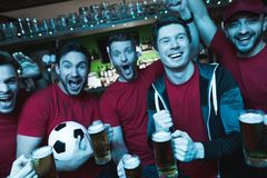 Soccer fans celebrating and cheering in front of tv drinking beer at sports bar. Soccer fans celebrating and cheering in front of tv drinking beer at sports bar royalty free stock photo