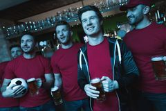 Soccer fans celebrating and cheering in front of tv drinking beer at sports bar. Soccer fans celebrating and cheering in front of tv drinking beer at sports bar stock photography
