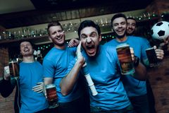 Soccer fans celebrating goal and cheering in front of tv drinking beer at sports bar. They are supporting blue team royalty free stock photos