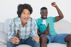 Soccer fans cheering while watching tv. Two excited soccer fans cheering while watching tv Stock Photography
