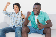Soccer fans cheering while watching tv. Two excited soccer fans cheering while watching tv Stock Photo