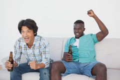 Soccer fans cheering while watching tv. Two excited soccer fans cheering while watching tv Stock Images