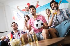 Soccer fans emotionally watching game in the living room. Soccer fans emotionally watching game and screaming in the living room Stock Photo