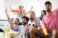 Soccer fans emotionally watching game in the living room. Soccer fans emotionally watching game and screaming in the living room Royalty Free Stock Images