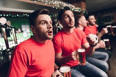 Soccer fans freeze in anticipation waiting for goal at sports bar. They are supporting red team royalty free stock photos