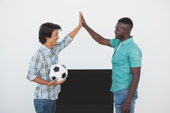 Soccer fans high fiving while watching tv Royalty Free Stock Images
