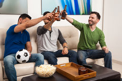 Soccer fans making a toast with beer. Group of soccer fans watching a game and making a toast to celebrating a goal Royalty Free Stock Photo