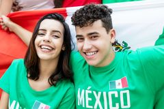 Soccer fans from Mexico with mexican flag looking at camera. Outdoors at stadium stock images