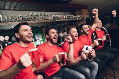 Soccer fans sitting in line celebrating and cheering drinking beer at sports bar. They are supporting red team stock photo
