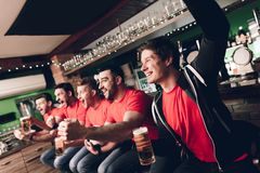 Soccer fans sitting in line celebrating and cheering drinking beer at sports bar. They are supporting red team royalty free stock photography