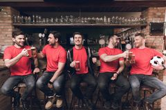Soccer fans watching the game drinking beer at sports bar. They are supporting red team Stock Image