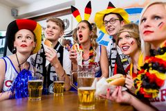 Soccer fans watching a game of the German national team. Waring all kinds of accessories stock image