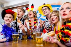Soccer fans watching a game of the German national team. Waring all kinds of accessories stock photography