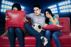 Soccer fans watching tv 1. Soccer fans watching tv and showing fear expression for lose Royalty Free Stock Images
