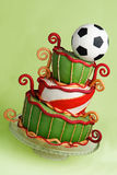 Soccer fantasy cake. Crooked curly cake in green, white, gold and red in soccer theme, with a football on top. Handmade cake with rolled fondant and sugar paste Royalty Free Stock Image