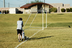Soccer field. A young boy stripes the soccer field before a game Stock Photo