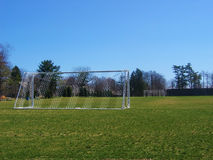 Soccer Field. Bright green soccer field with net and blue sky background stock photos