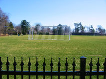 Soccer Field. Bright green soccer field with net and blue sky background and black iron fence stock image