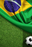 Soccer field with ball and flag of Brazil. Soccer field top view with ball and flag of Brazil Royalty Free Stock Photo