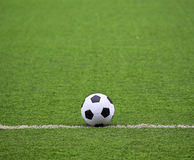 Soccer field with ball. White stripe on the green soccer field with ball Royalty Free Stock Photo