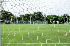 Soccer field from behind goal net Royalty Free Stock Photography