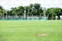 Soccer field from behind goal net Royalty Free Stock Image