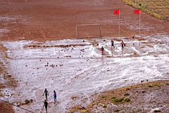 A soccer field with children playing football after the rain  in Atlas mountains in Morocco Royalty Free Stock Photo