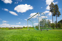 Soccer field and empty net. Against blue sky and white clouds, trees in the background Stock Photo