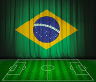 Soccer field with flag of Brazil on green curtain  Royalty Free Stock Photography