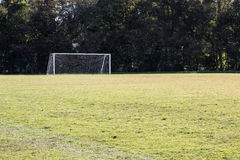 Soccer Field with Goal. Empty soccer field with background of a soccer goal and trees Royalty Free Stock Photos