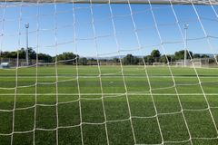 Football field in a sport complex. Soccer field through the goal net in a sports complex stock photo