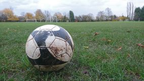 A close up of a football on the ground. Soccer field green goalkeepers black pattern area penalty box grass brown mud white line mouth between the sticks over on Stock Photography