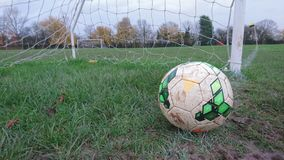 A football on the goal line of a muddy football pitch. Soccer field green grass brown mud white line mouth between the sticks over on resting netting score saved Stock Images