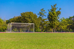 Soccer field and white goal with trees and blue sky background. Empty green grass soccer field and white goal with trees and blue sky background Stock Image