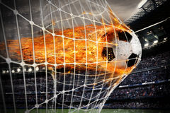 Soccer fireball scores a goal on the net. Professional soccer fireball leaves trails of flames and scores a goal on the net stock photo