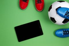 Soccer football background. Top view of two soccer players shoes, soccer ball and tablet computer on green background stock images