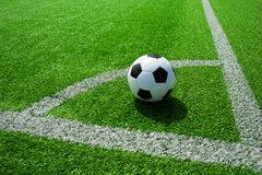 Soccer, football, ball, on corner spot, white marks, classic black and white on clean green field, space for text, good for banner. Soccer ball black and white stock image