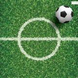 Soccer football ball on green grass of soccer field pattern. Soccer football ball on green grass of soccer field pattern and texture background with center line Stock Photos
