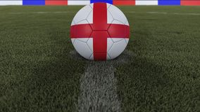 Soccer / football classic ball in the center of the field grass with painting of the England flag  with depth of field defocused,. Soccer / football classic ball Royalty Free Stock Image