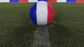 Soccer / football classic ball in the center of the field grass with painting of the France flag with depth of field defocused, 3D. Soccer / football classic Stock Photo