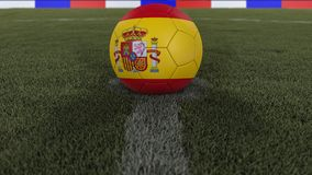 Soccer / football classic ball in the center of the field grass with painting of the Spain flag  with depth of field defocused, 3D. Soccer / football classic Royalty Free Stock Photos
