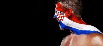 Soccer or football fan with bodyart on face with agression - flag of Croatia. Football of fan are cheering for their team victory royalty free stock image