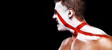 Soccer or football fan with bodyart on face with agression - flag of England. royalty free stock image
