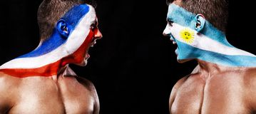Soccer or football fan with bodyart on face with agression - flag of France vs Argentina. Football of fan are cheering for their team victory royalty free stock photo
