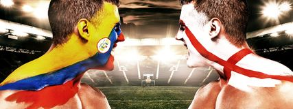 Soccer or football fan with bodyart on face with agression - flags of Colombia vs England. royalty free stock photo