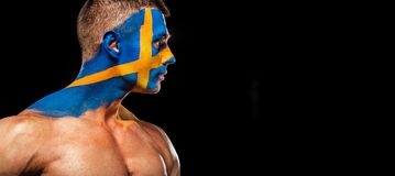 Soccer or football fan with bodyart on face - flag of Sverige. Stock Photos