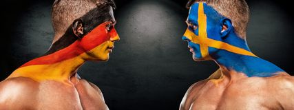 Deutschland vs Sverige. Two soccer or football fans with flags face to face on stadium. Soccer or football fan with bodyart on face on stadium. Russia 2018 Royalty Free Stock Photography