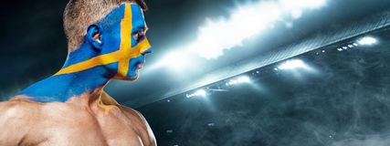 Soccer or football fan on stadium with bodyart on face - flag of Sverige. Soccer or football fan with bodyart on face on stadium. Russia 2018 Royalty Free Stock Photography