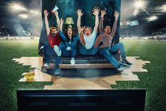 Soccer football fans sitting on the sofa and watching TV in the middle of a football field. royalty free stock photo